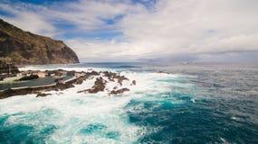 Ondas e rochas perto das associações da cidade da opinião aérea de Porto Moniz fotografia de stock