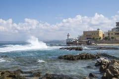 Ondas en la costa con el faro viejo en el neumático, amargo, Líbano Foto de archivo libre de regalías