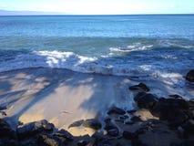 Ondas en una playa con la roca volcánica en Hawaii Fotografía de archivo