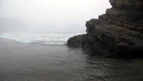 Ondas encobertas névoa que movem ao redor a grande rocha vídeos de arquivo
