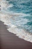 Ondas espumadas que quebram na praia fotos de stock