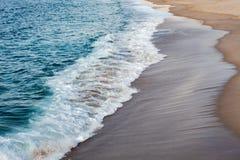 Ondas espumadas que quebram na praia imagens de stock royalty free