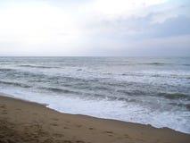 Ondas espumosas da cor branca no oceano cinzento da cor no Sandy Beach marrom Foto de Stock Royalty Free