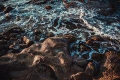 Ondas espumosas en la playa rocosa fotos de archivo