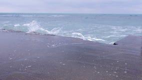 Ondas fuertes de la tormenta que baten contra el rompeolas en la costa, chapoteo del agua almacen de metraje de vídeo