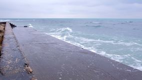 Ondas fuertes de la tormenta que baten contra el rompeolas en la costa, chapoteo del agua Escaleras que entran el mar agitado car metrajes