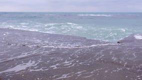 Ondas fuertes de la tormenta que baten contra el rompeolas en la costa, chapoteo hermoso del agua almacen de metraje de vídeo