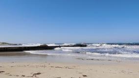 Ondas fuertes del mar que golpean contra el embarcadero y la playa arenosa en un día ventoso soleado Clima tempestuoso de la play almacen de video