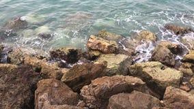Ondas fuertes que salpican sobre piedras Ondas del mar que golpean el océano rocoso de la costa que salpica contra rocas almacen de metraje de vídeo