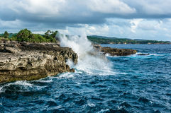 Ondas grandes que se rompen y que salpican en las rocas Fotografía de archivo