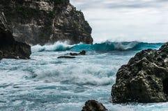 Ondas grandes que se rompen y que salpican en las rocas Fotos de archivo