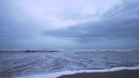 Ondas hermosas del mar en la cámara lenta en la arena de la playa en la puesta del sol azul almacen de metraje de vídeo