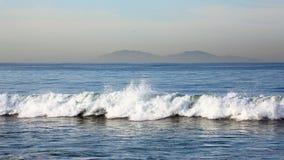 Ondas a lo largo de la playa con las islas en el fondo Imagen de archivo libre de regalías