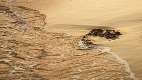 Ondas macias do mar que apressam-se no por do sol Imagem de Stock