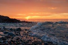 Ondas macias em uma praia rochosa do por do sol Imagens de Stock Royalty Free