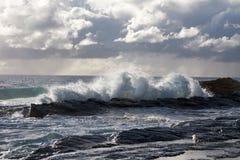 Ondas medias que se estrellan en las rocas con las nubes de tormenta Imágenes de archivo libres de regalías