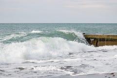 Ondas no mar perto do cais nublado Imagem de Stock Royalty Free