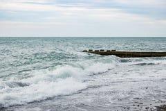 Ondas no mar perto do cais nublado Fotos de Stock