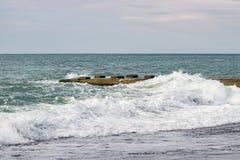 Ondas no mar perto do cais nublado Fotografia de Stock
