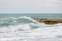 Ondas no mar perto do cais nublado Imagem de Stock