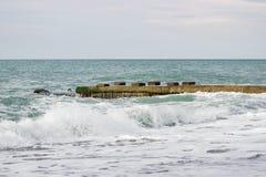 Ondas no mar perto do cais nublado Foto de Stock Royalty Free