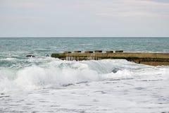 Ondas no mar perto do cais nublado Foto de Stock