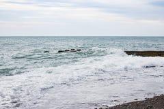 Ondas no mar perto do cais nublado Imagens de Stock