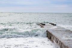 Ondas no mar perto do cais nublado Imagens de Stock Royalty Free