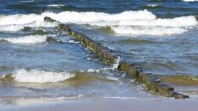 Ondas pequenas do mar com quebra-mar de madeira e Sandy Beach limpo imagens de stock