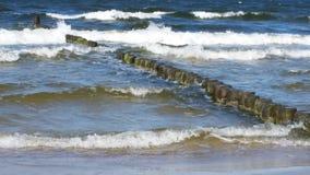Ondas pequenas do mar com quebra-mar de madeira e a Sandy limpa fotos de stock