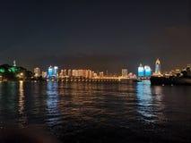 Ondas pequenas do parque de Qingdao e cenário distante da noite da cidade imagem de stock royalty free