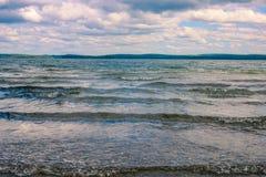 Ondas pequenas no lago sob o céu nebuloso pesado Paisagem da natureza fotos de stock