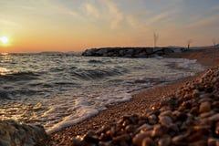 Ondas pequenas que entram a linha costeira durante a hora dourada ao longo da costa Fotografia de Stock