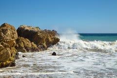 Ondas que batem contra rochas litorais nos penhascos Foto de Stock