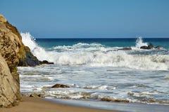 Ondas que batem contra rochas litorais nos penhascos Fotos de Stock