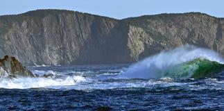 Ondas que batem paredes do penhasco na angra média em Terra Nova foto de stock