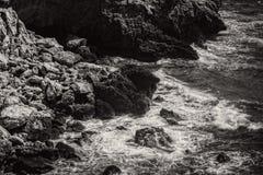 Ondas que batem rochas em preto e branco foto de stock