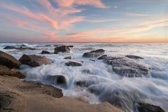 Ondas que causan un crash en la playa rocosa imagen de archivo