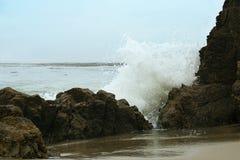 Ondas que causan un crash en las rocas en la playa Imagen de archivo libre de regalías