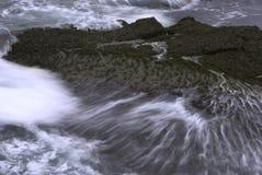 Ondas que causan un crash en rocas Foto de archivo