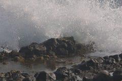 Ondas que causan un crash sobre rocas Imagenes de archivo