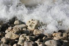 Ondas que causan un crash sobre rocas en una playa Foto de archivo