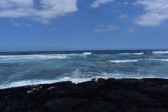 Ondas que deixam de funcionar em uma praia rochosa preta fotografia de stock