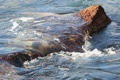 Ondas que espirram sobre a rocha Fotografia de Stock