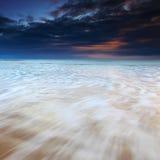 Ondas que fluyen sobre la playa en la salida del sol Imagen de archivo libre de regalías