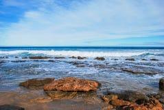 Ondas que hunden hacia las rocas, océano azul perfecto, rocas en la orilla, nubes de altostrato en el cielo fotografía de archivo