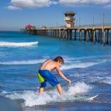 Ondas que practican surf de la persona que practica surf del muchacho en la playa de Huntinton Imagen de archivo libre de regalías