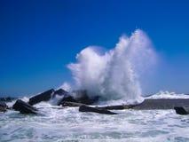 Ondas que quebram no quebra-mar concreto no céu azul claro na fotografia de stock