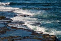 Ondas que salpican sobre costa rocosa en Australia Foto de archivo