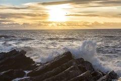 Ondas que se estrellan contra costa en la salida del sol Fotos de archivo libres de regalías